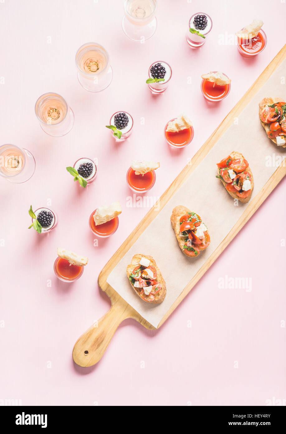 Snacks, brushetta sandwiches, gazpacho shots, desserts over pastel pink background - Stock Image