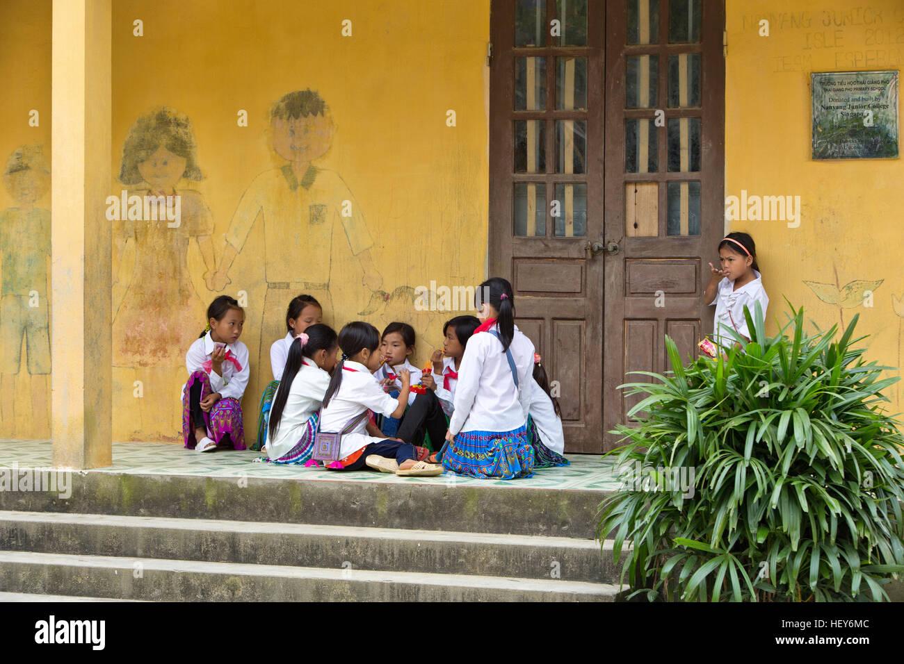 Young girls communicating & enjoying a snack during school break. - Stock Image