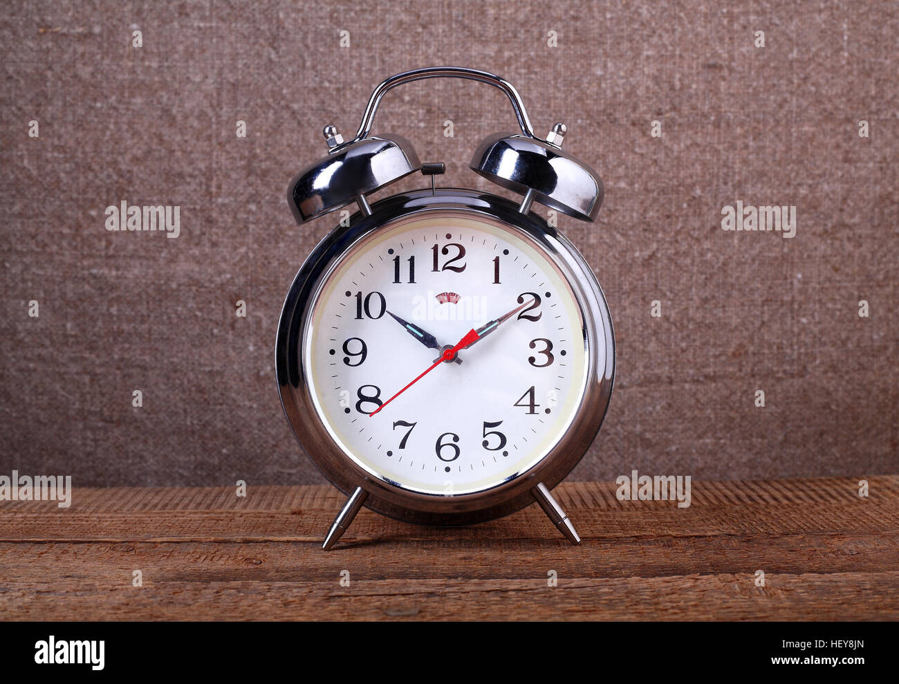 Clock - Vintage old alarm clock on sackings and a wooden background. Stock Photo