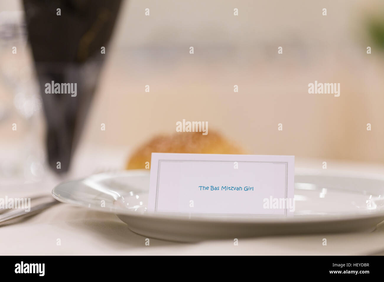 Black and white theme table setting with bat mitzvah girl label and challah bread roll - Stock Image