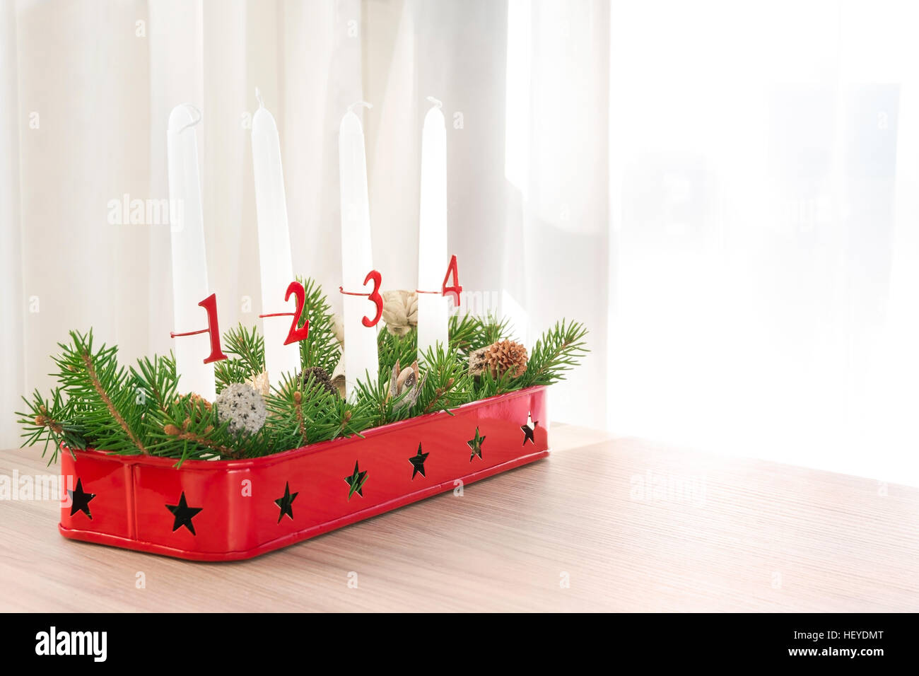 Red Christmas advent wreath with decoration on table against light background - Stock Image