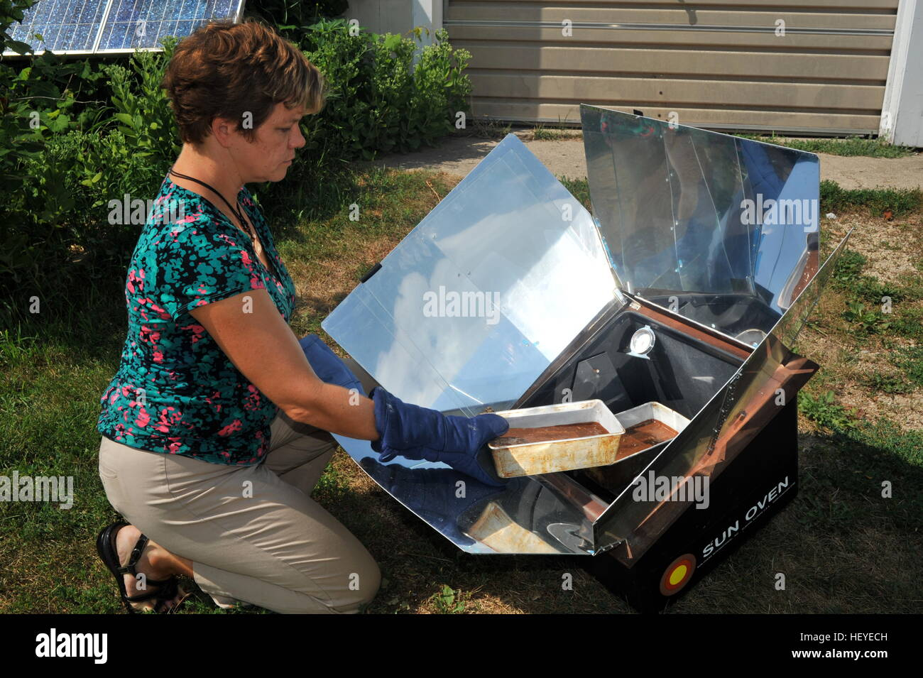Woman cooking or baking fresh zucchini bread with a Sun Oven outside, using the sunlight for the baking. Stock Photo
