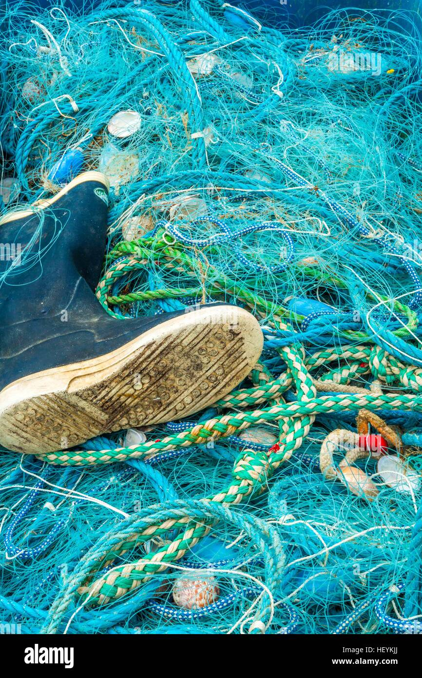 a wellington boot and a fishing net at Newquay Harbour, Cornwall, UK - Stock Image