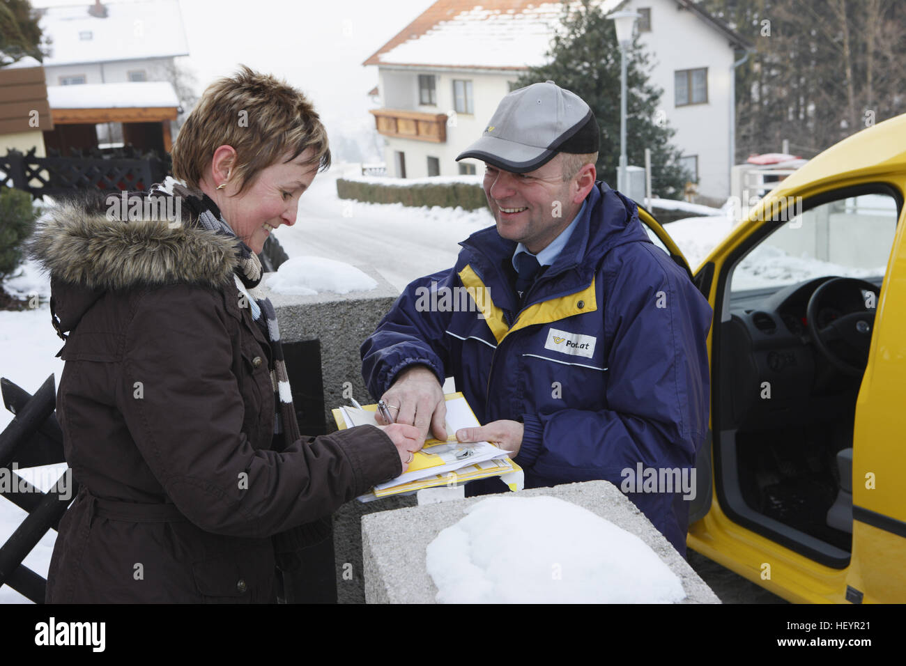 Mailman (Mail carrier, letter carrier) handing package to a woman - Stock Image