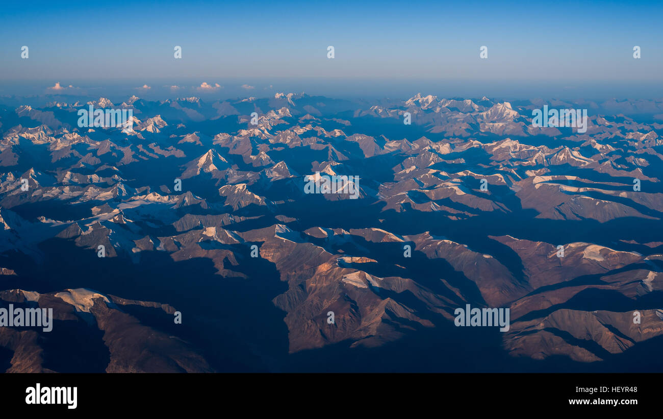 Snow mountain range with sunrise morning from airplane - Stock Image
