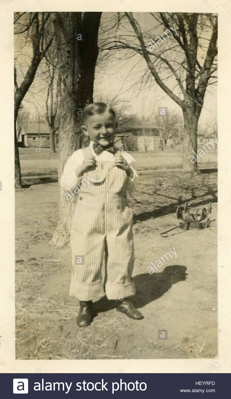 smiling little boy standing outside in the vintage photographs from