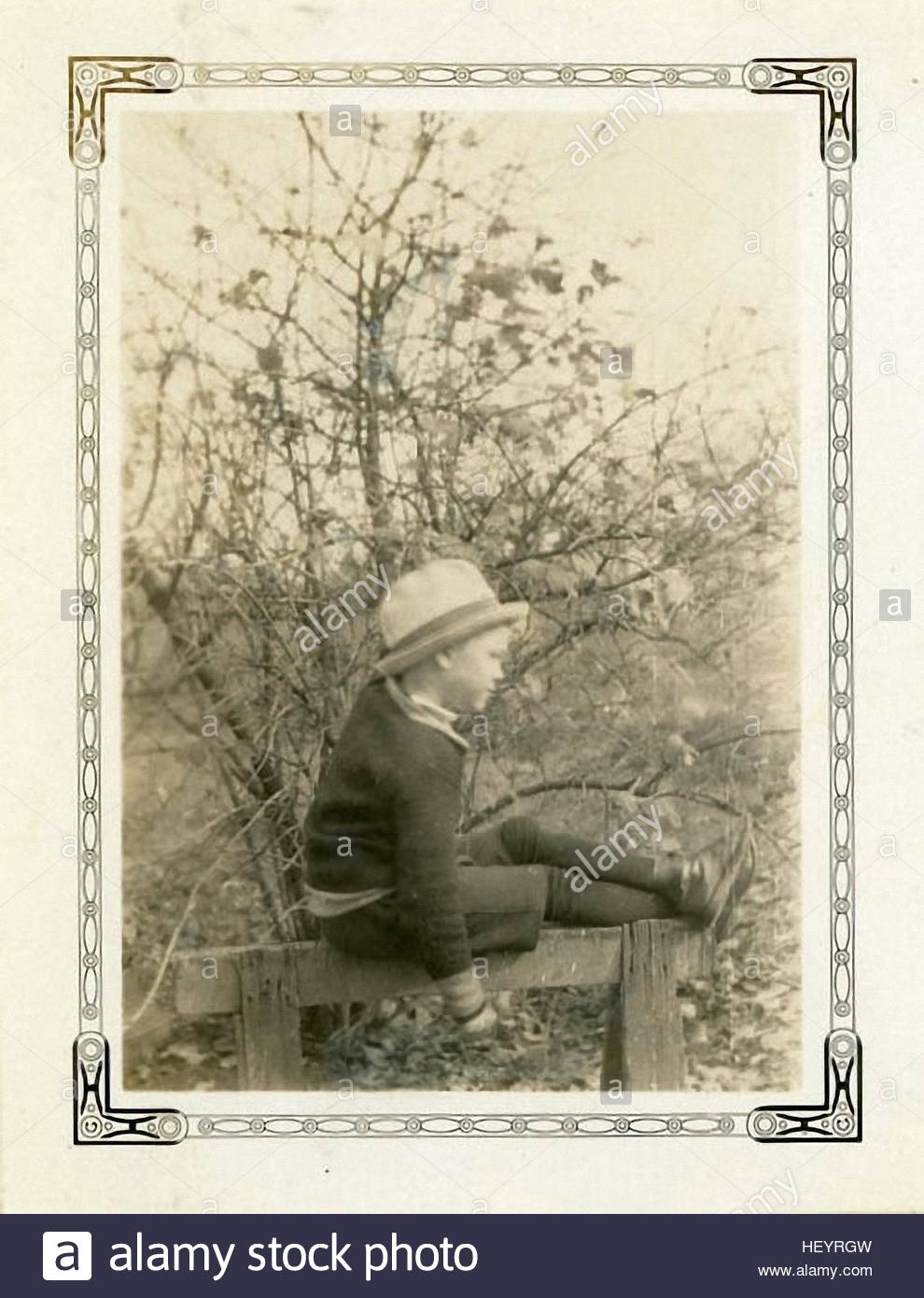 adorable young boy sitting on the edge of the char on the vintage photography from the 30s - Stock Image
