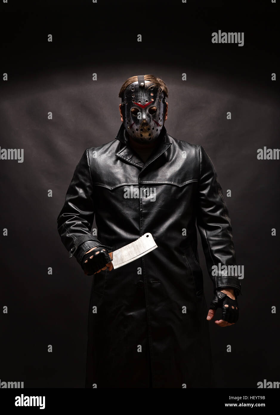 Bloody murderer in hockey mask with meat cleaver - Stock Image