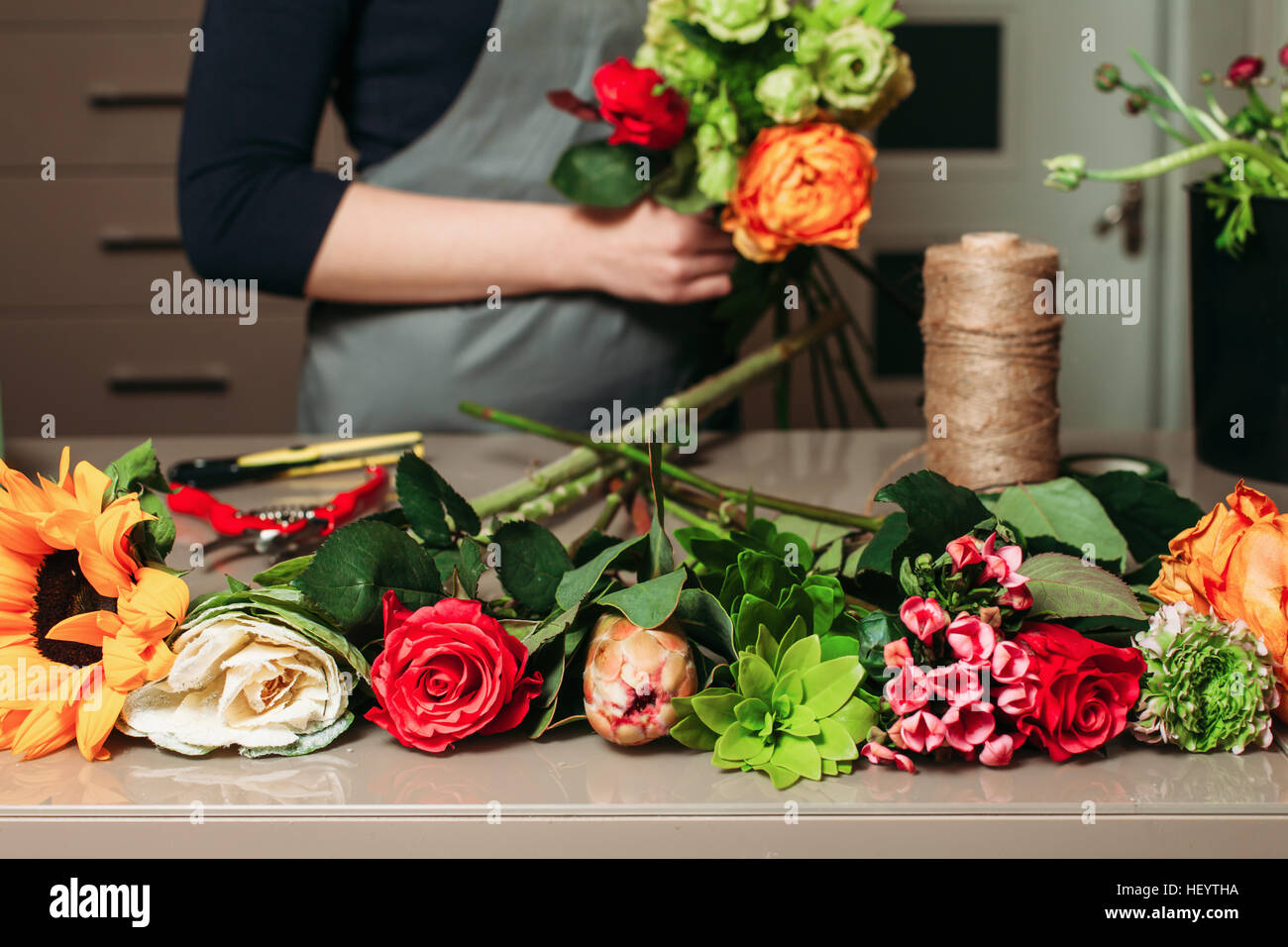 Florist with bouquet of roses at work. - Stock Image