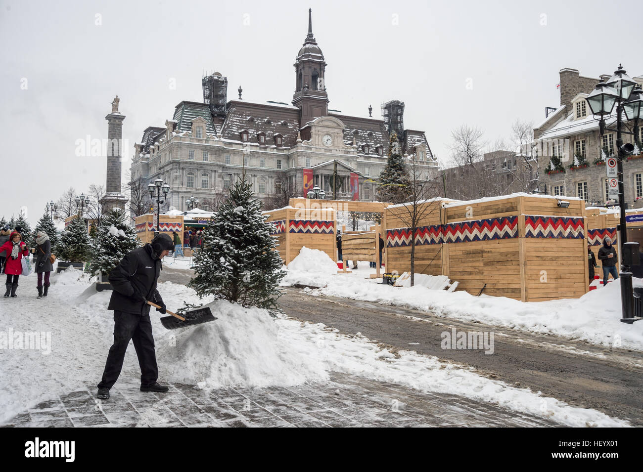 Montreal, CA - 17 December 2016: Man with snow shovel cleans sidewalk during Christmas market on Place Jacques Cartier - Stock Image