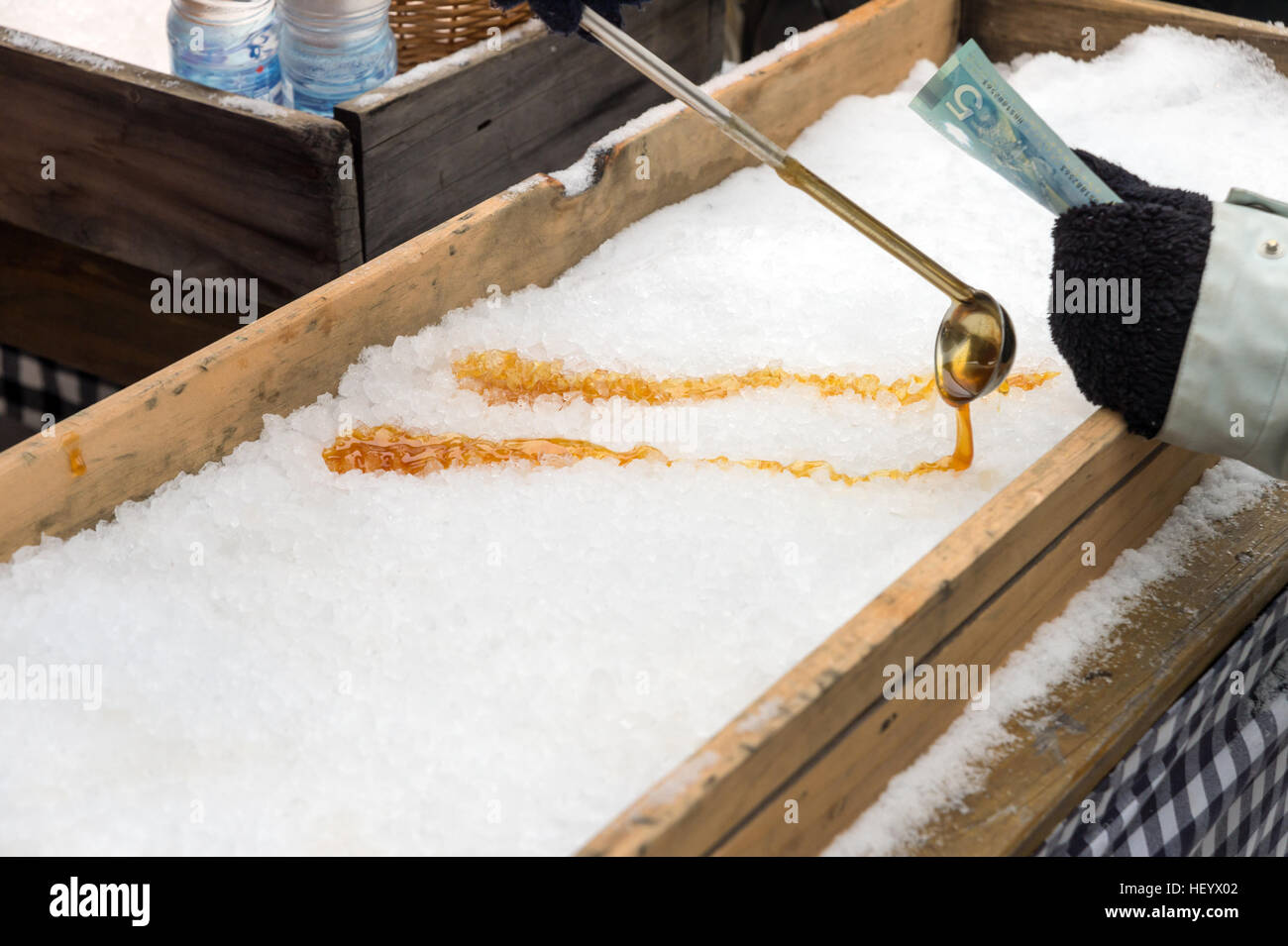 Montreal, CA - 17 December 2016: Maple taffy on snow in Montreal, Quebec, Canada, with someone waiting to pay - Stock Image