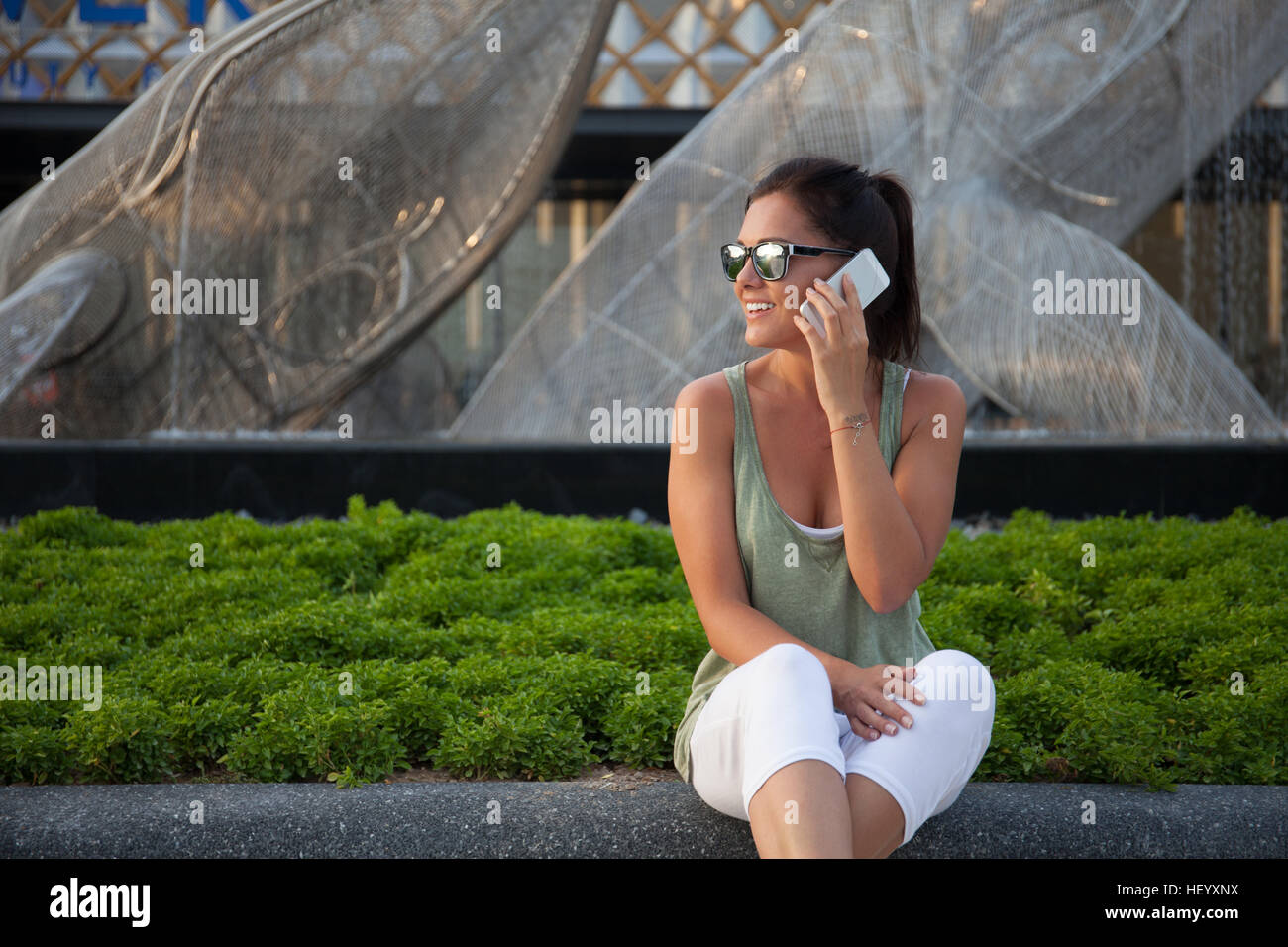 Young girl talks on the smartphone, she is wearing white trousers, green t-shirt and sunglasses - Stock Image