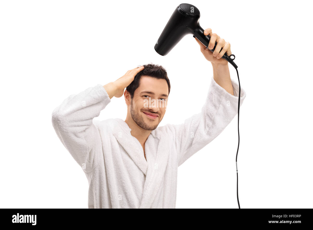 Young guy in a bathrobe drying his hair with a hairdryer isolated on white background - Stock Image