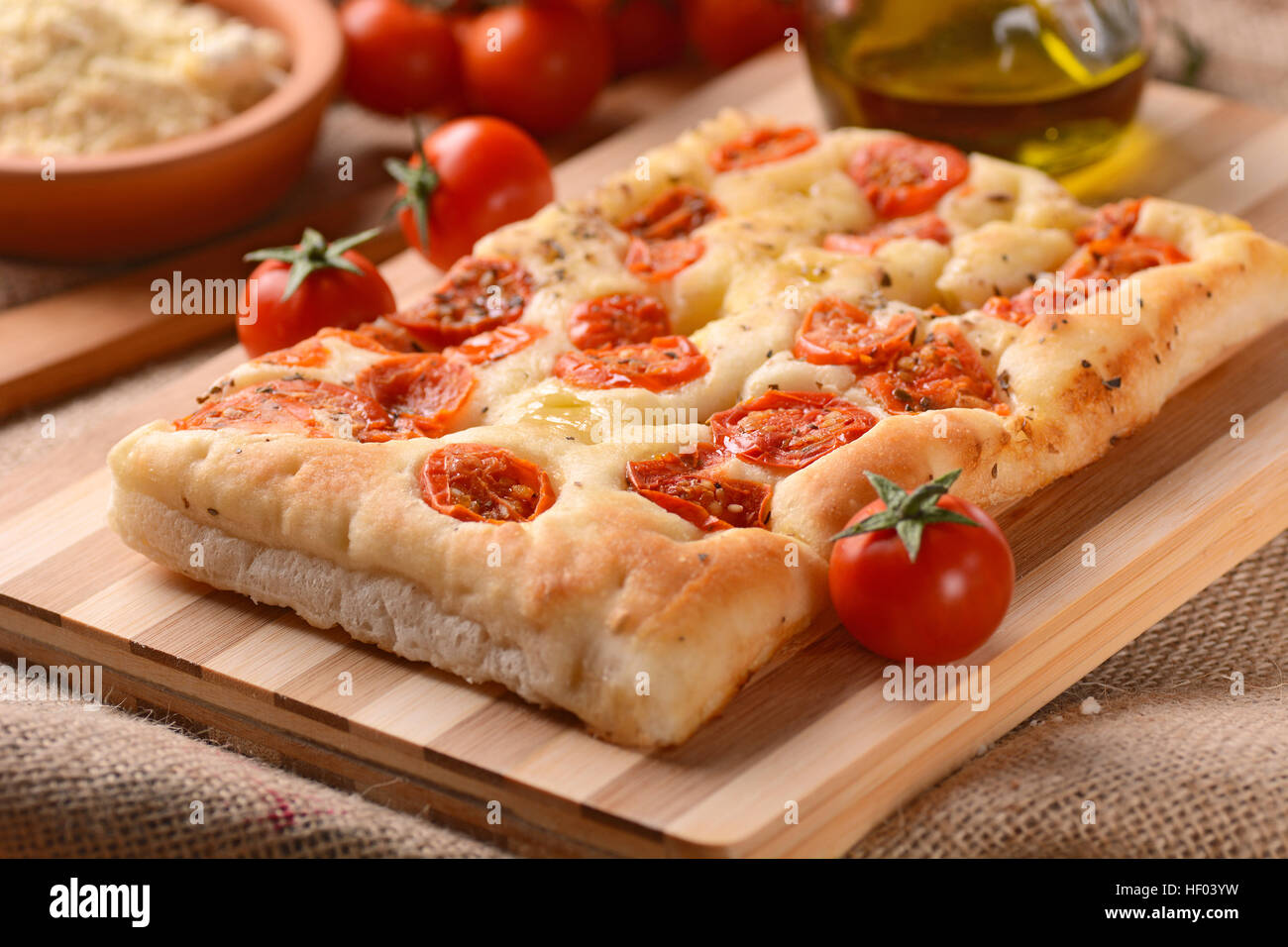 flat bread with cherry tomatoes on wooden chopping board - Stock Image