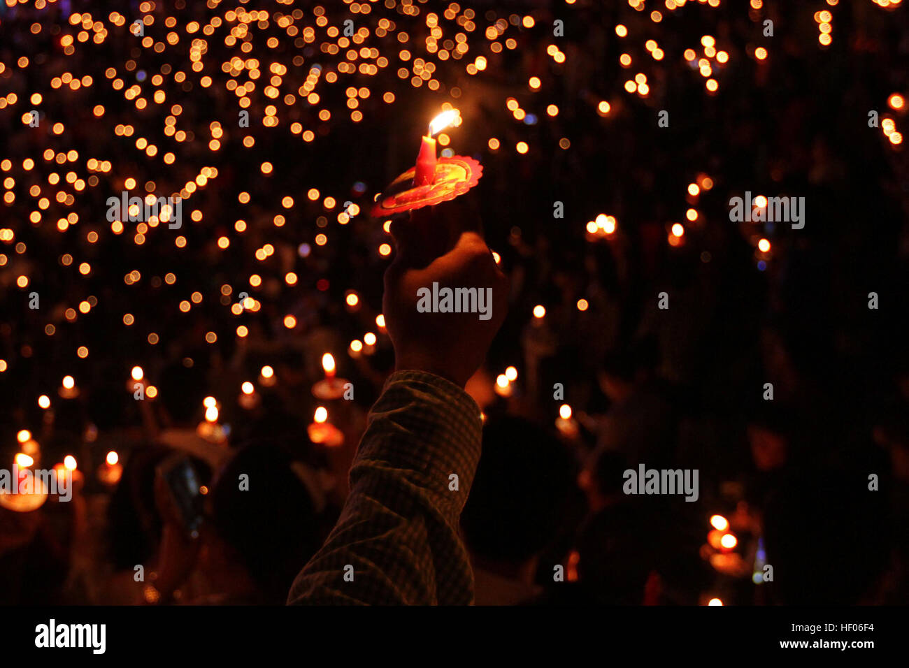 Palembang, Indonesia. 24th Dec, 2016. People hold candles while celebrating the Christmas Eve at a church in Palembang, - Stock Image