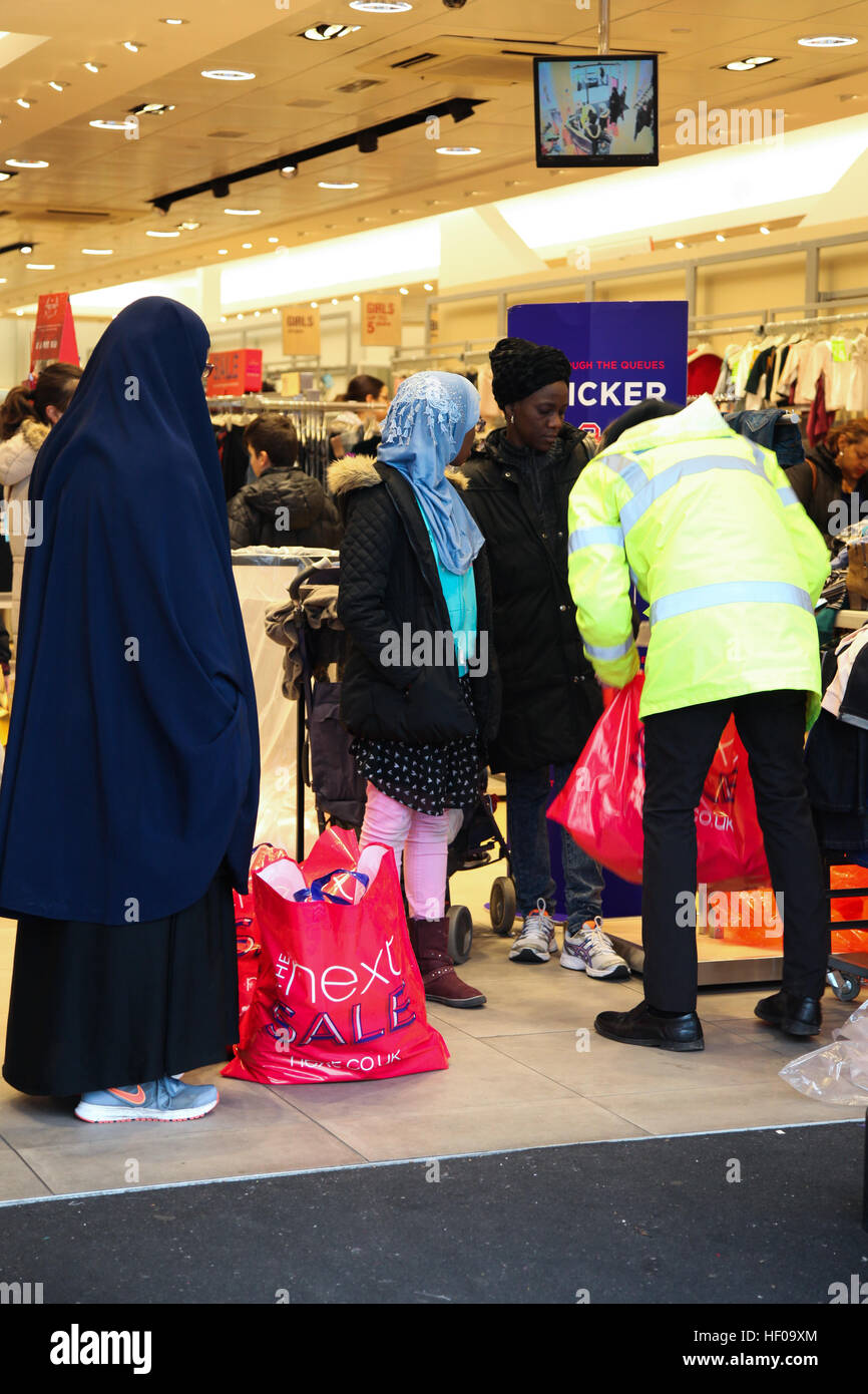 Arena Retail Park, Harringay, North London, UK. 26 Dec 2016 Shoppers hold multiple bags at Next in Arena Retail Stock Photo