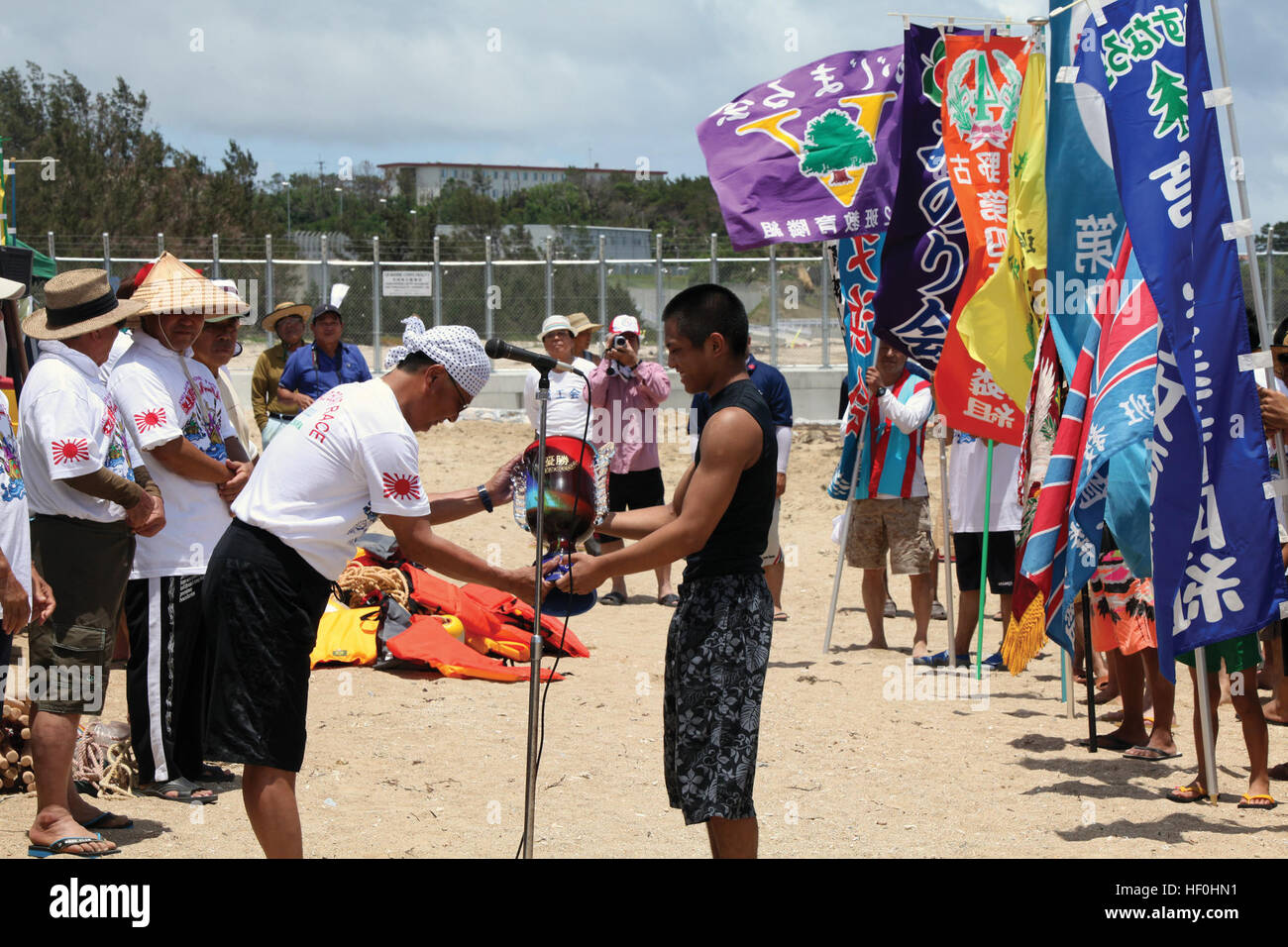 A member of last year's championship team hands over the trophy to a Henoko District official during the annual - Stock Image