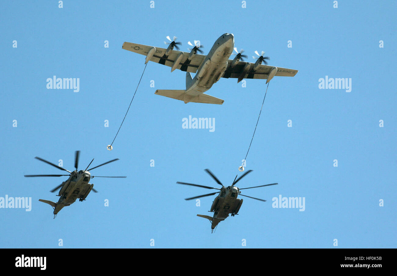 A KC-130J Hercules plane performs a simulated refueling mission for two CH-53E Super Stallion helicopters over the - Stock Image