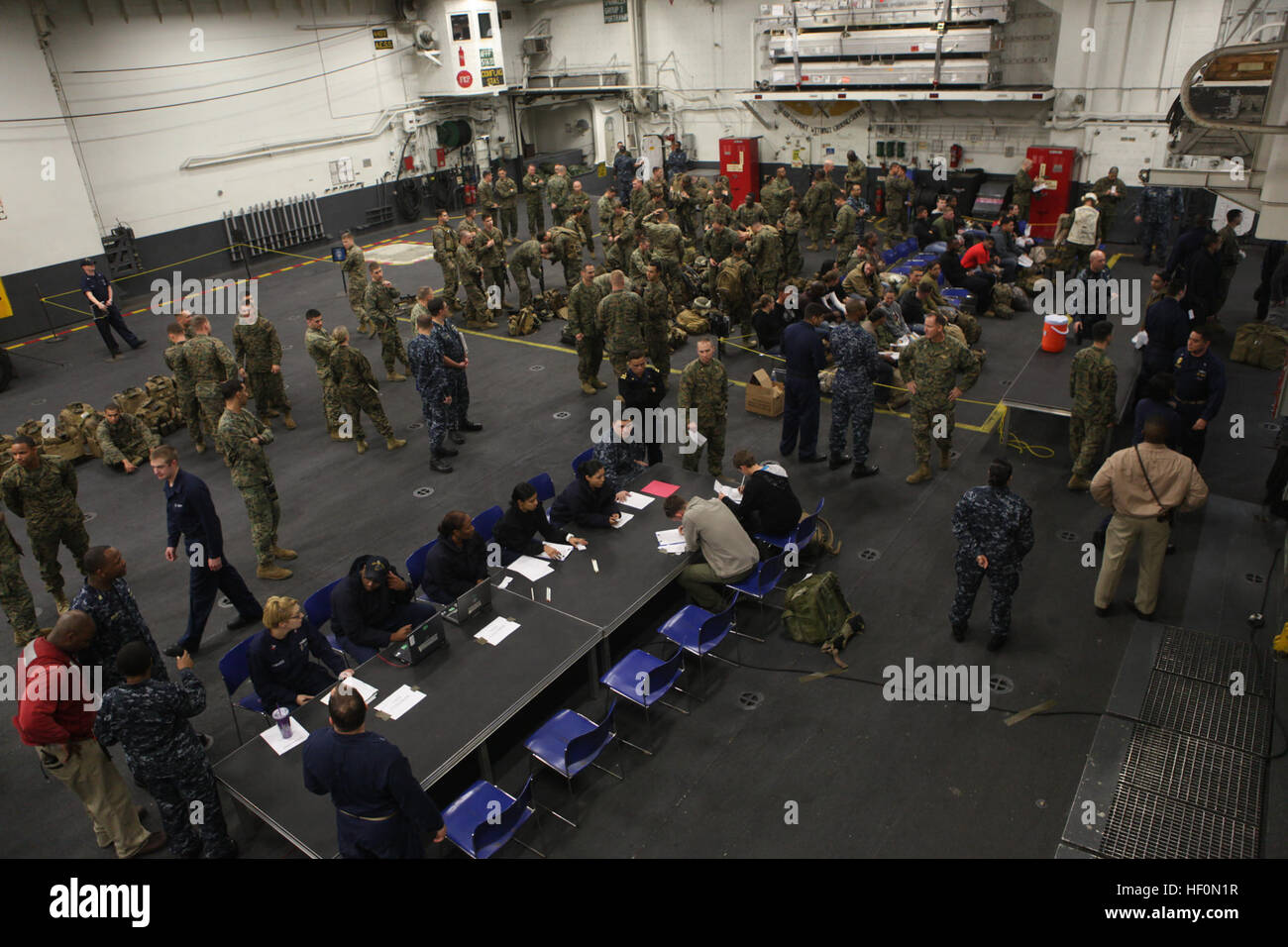 Role players are welcomed and processed aboard USS Iwo Jima after being evacuated by Marines and Sailors with 24th Stock Photo