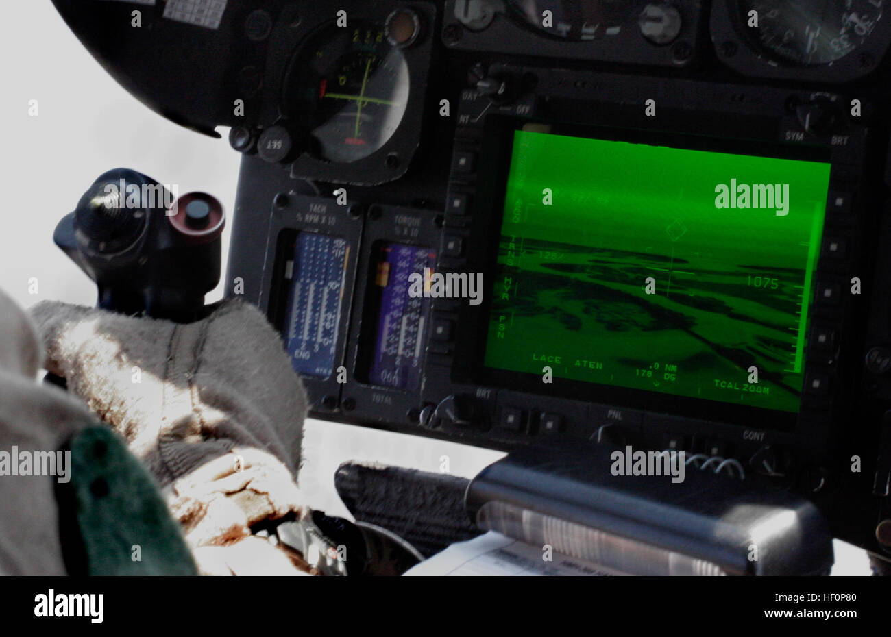 A pilot with HMH-366 monitors the ground below from the seat of a ...