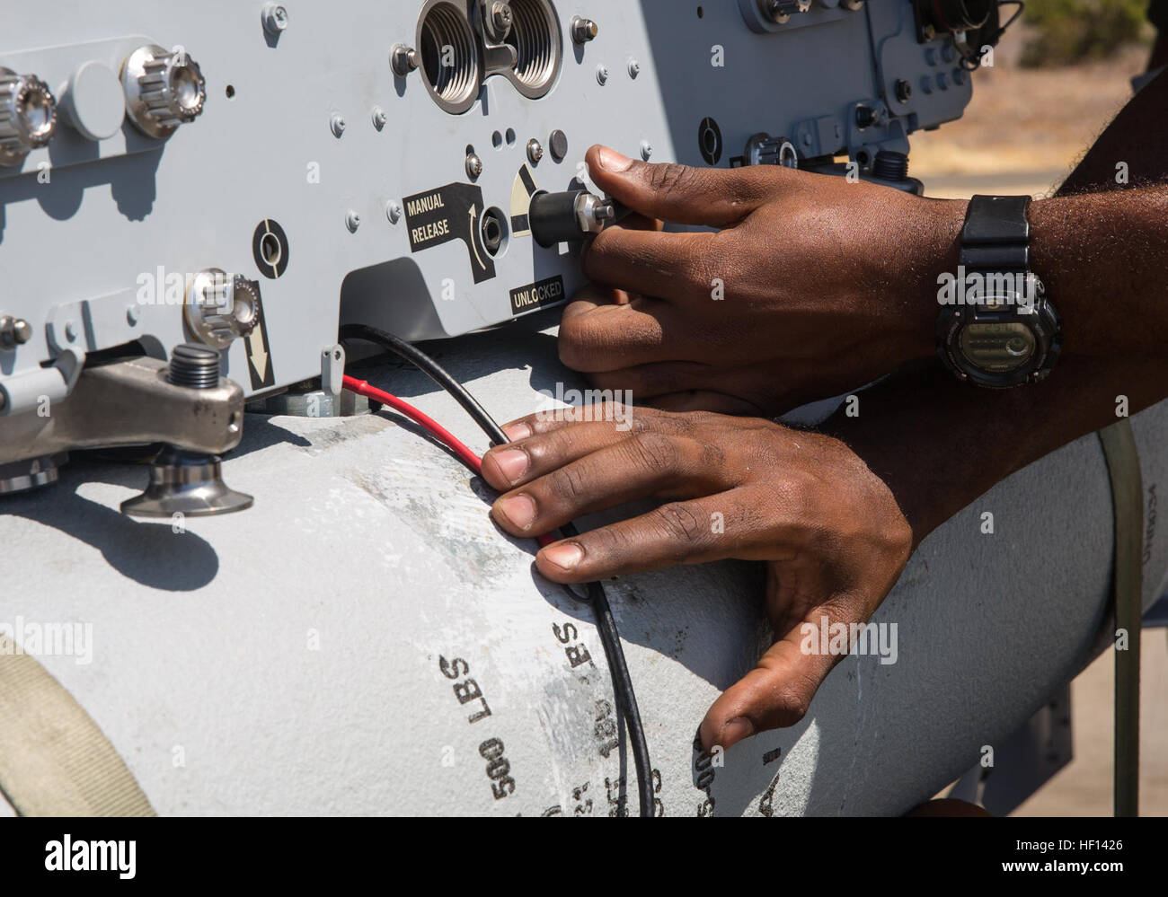 """An aviation ordnance Marine with Marine All-Weather Fighter Attack Squadron  (VMFA(AW)) 225 """"Vikings"""" locks in place a MK-82 low-drag bomb on an F/A-18  ..."""