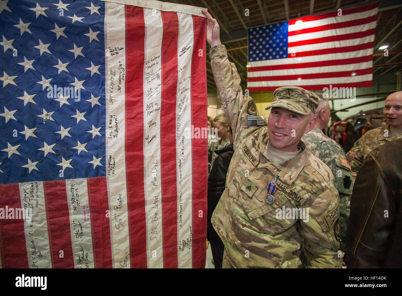 Sgt. Raymond J. Fulgoni holds up his flag, which is signed by the Soldiers of the 117th Combat Sustainment Support - Stock Image