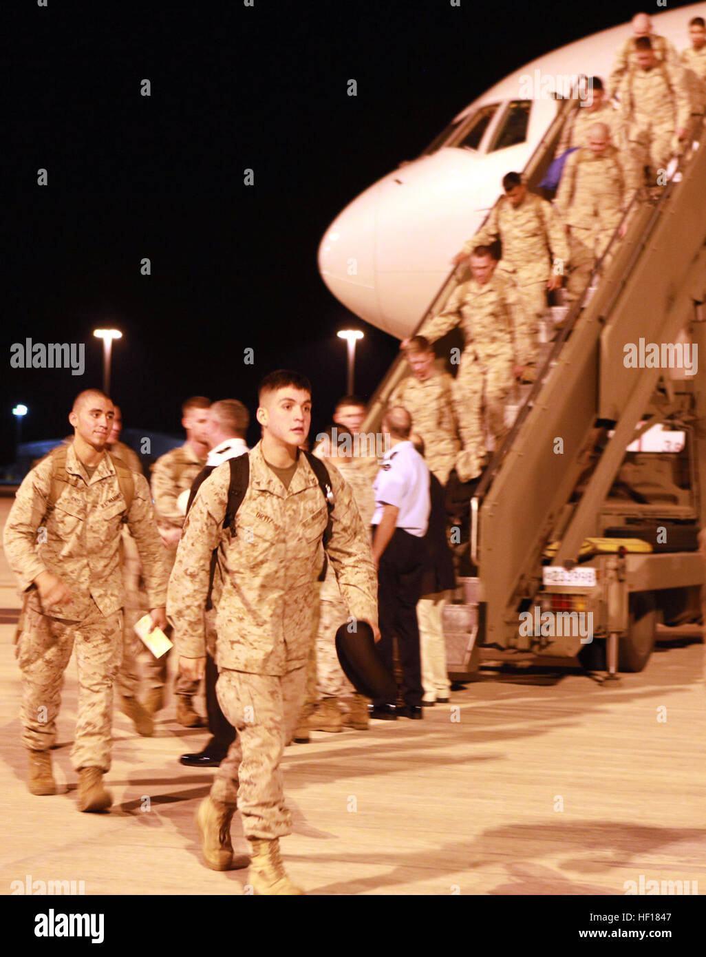 Marines with Lima Company, 3rd Battalion, 3rd Marine Regiment, depart the plane upon their arrival aboard RAAF Base Stock Photo