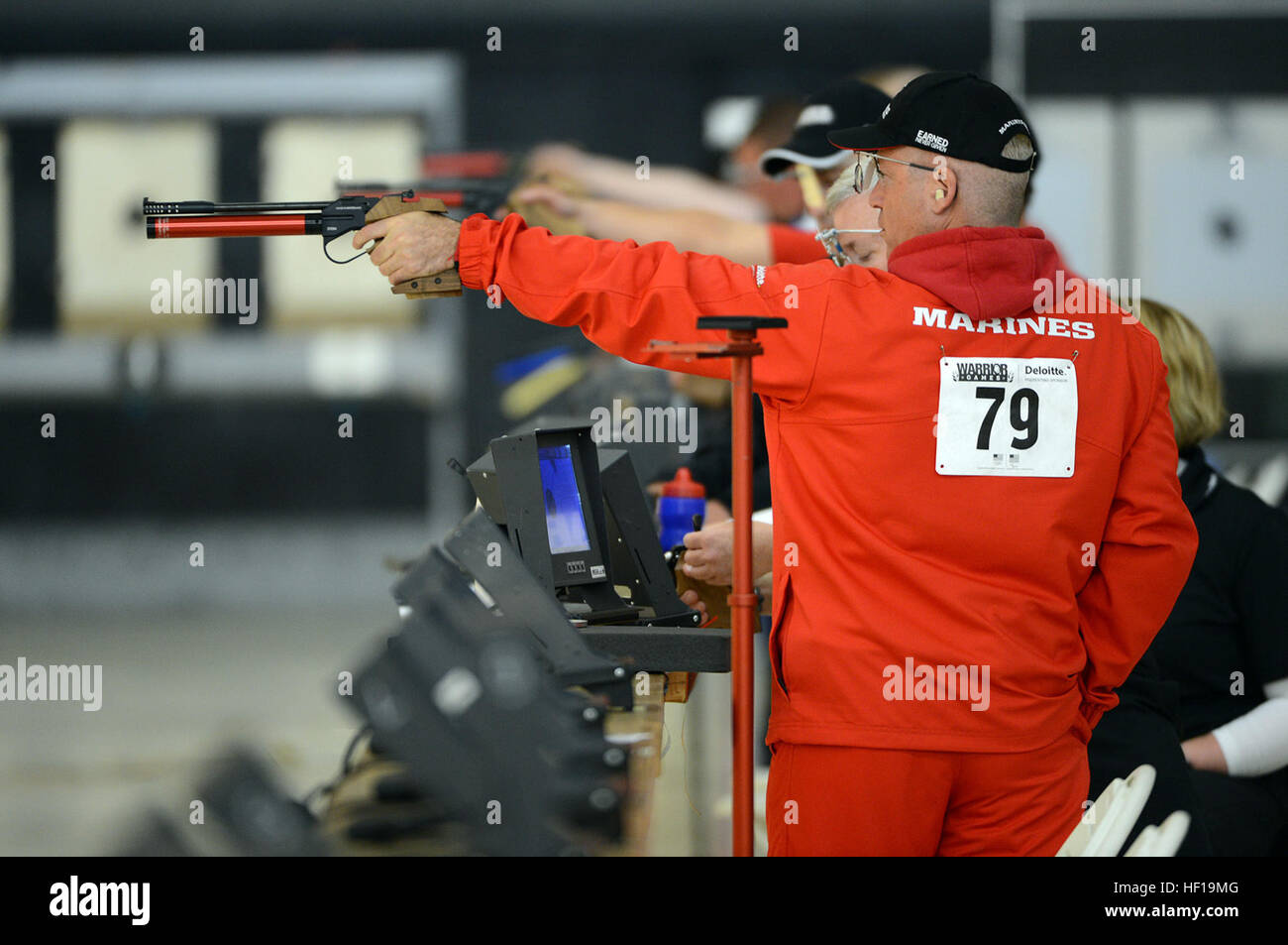 Marine veteran Master Sgt. Nicholas Dionisios shoots to win a pistol SH1 competition, which includes all competitors - Stock Image