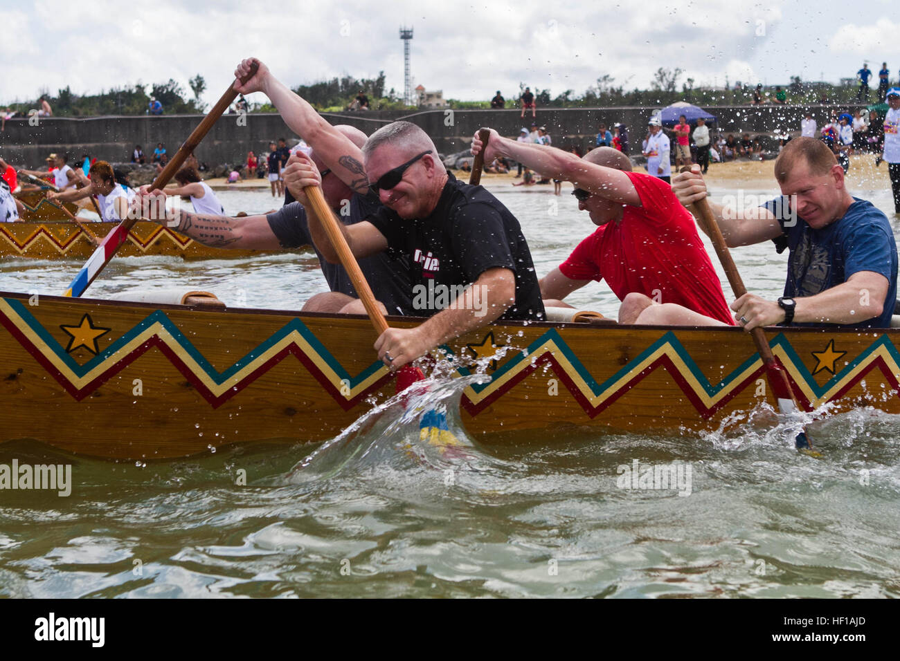 Marines and sailors with 3rd Battalion, 6th Marine Regiment, paddle through the water during the annual Henoko dragon - Stock Image