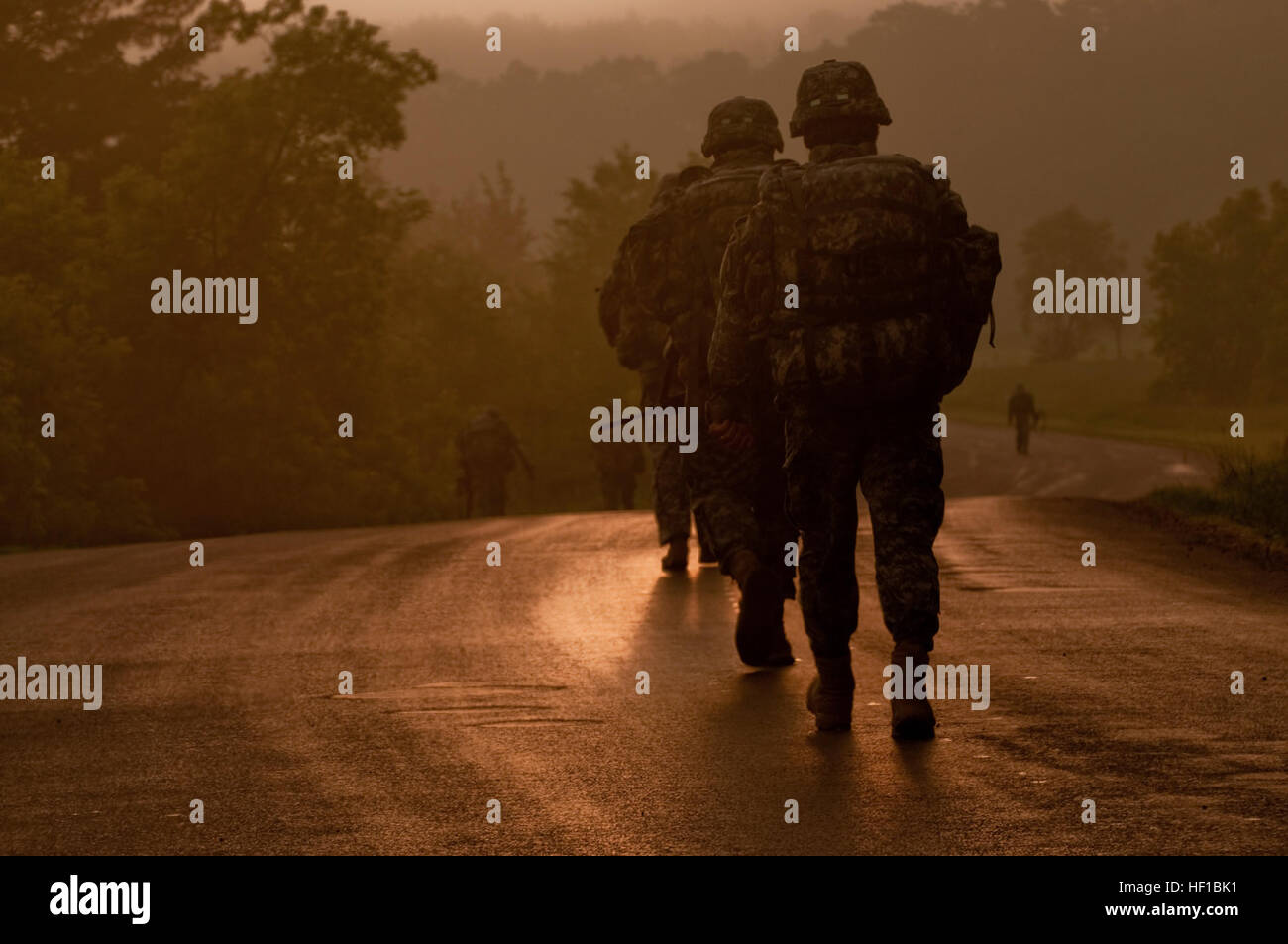 U.S. soldiers walk along at a quick pace into the rising sun during the 10 kilometer road march at the 2013 Army - Stock Image