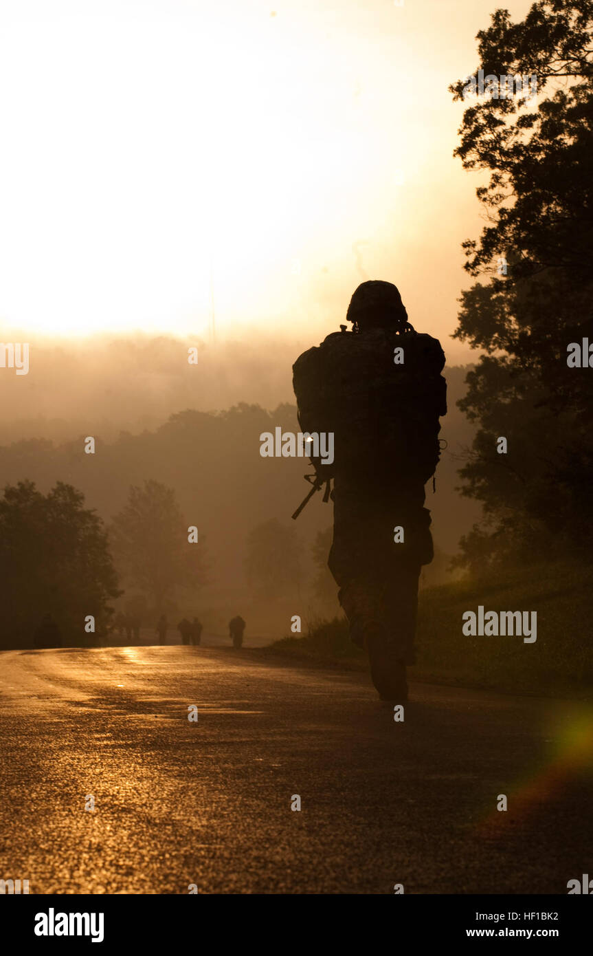 A U.S. soldier walk along at a quick pace into the rising sun during the 10 kilometer road march at the 2013 Army - Stock Image