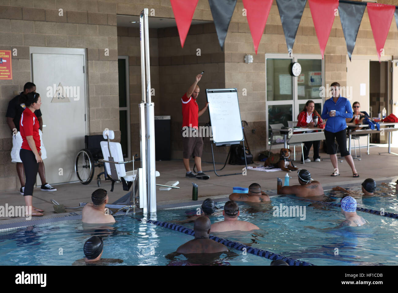 Head Coach Michael Kleinert provides instruction and demonstration to swimmers prior to beginning training on the - Stock Image