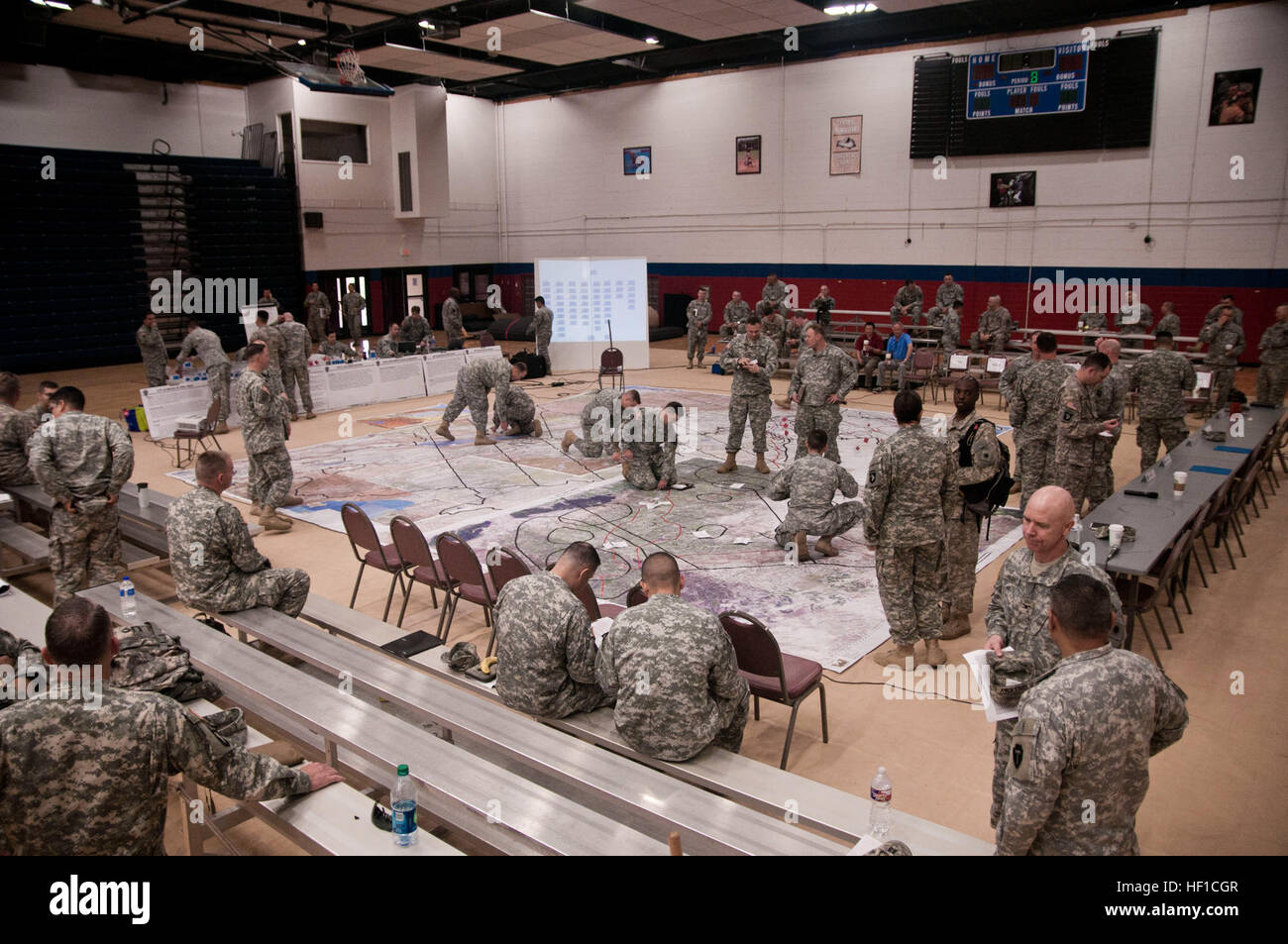 Soldiers from the 36th Infantry Division gather by a map board for a briefing in preparation for a simulated air - Stock Image