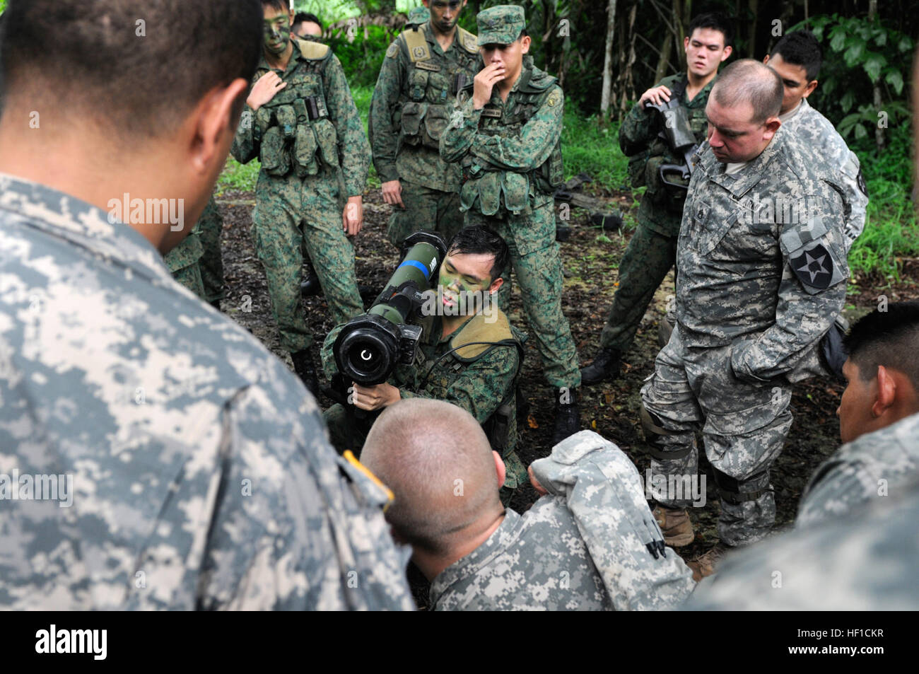 A soldier with Charlie Company, 2nd Battalion, Singapore Infantry Regiment, shows U.S. Soldiers from 4th Battalion, - Stock Image