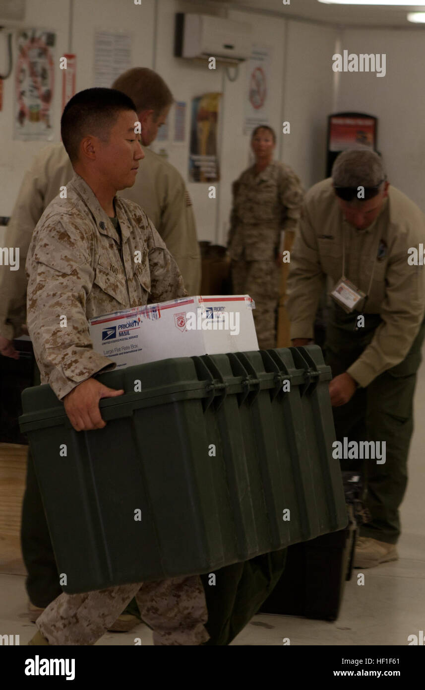 A Marine carries packages to the front counter at the post office aboard Camp Leatherneck, Afghanistan, where postal - Stock Image