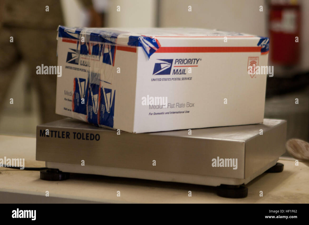 A package rests on a scale at the post office aboard Camp Leatherneck, Afghanistan, where postal Marines with Combat - Stock Image