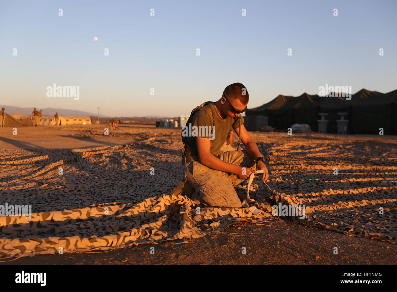 U.S. Marine Lance Cpl. Eric Trautman of Ravenna, Ohio, ties camouflage netting during a field exercise aboard Camp - Stock Image