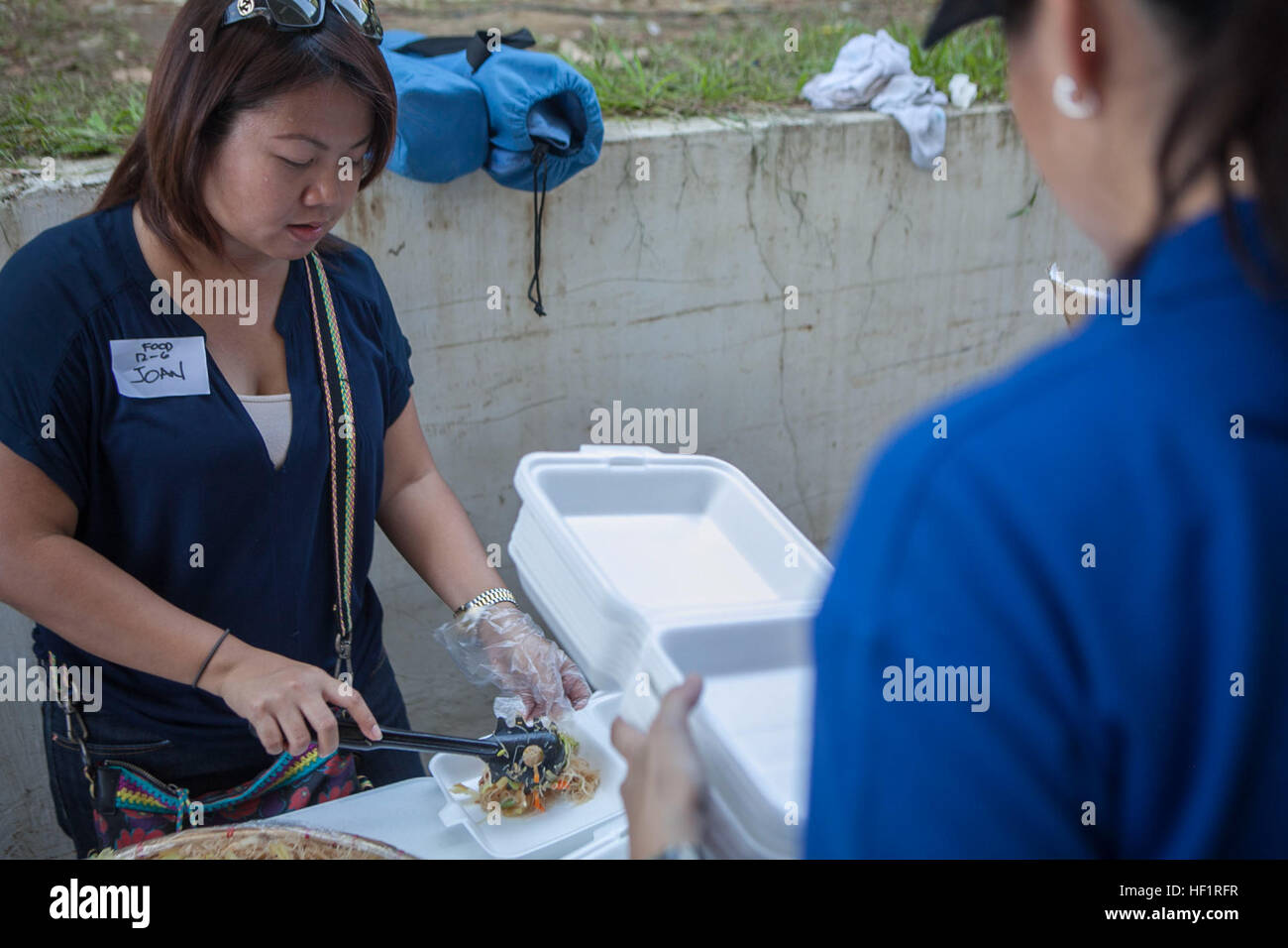 A volunteer serves food to evacuees here Nov. 17 as they deplane at Villamor Air Base. Marine Corps and other U.S. - Stock Image