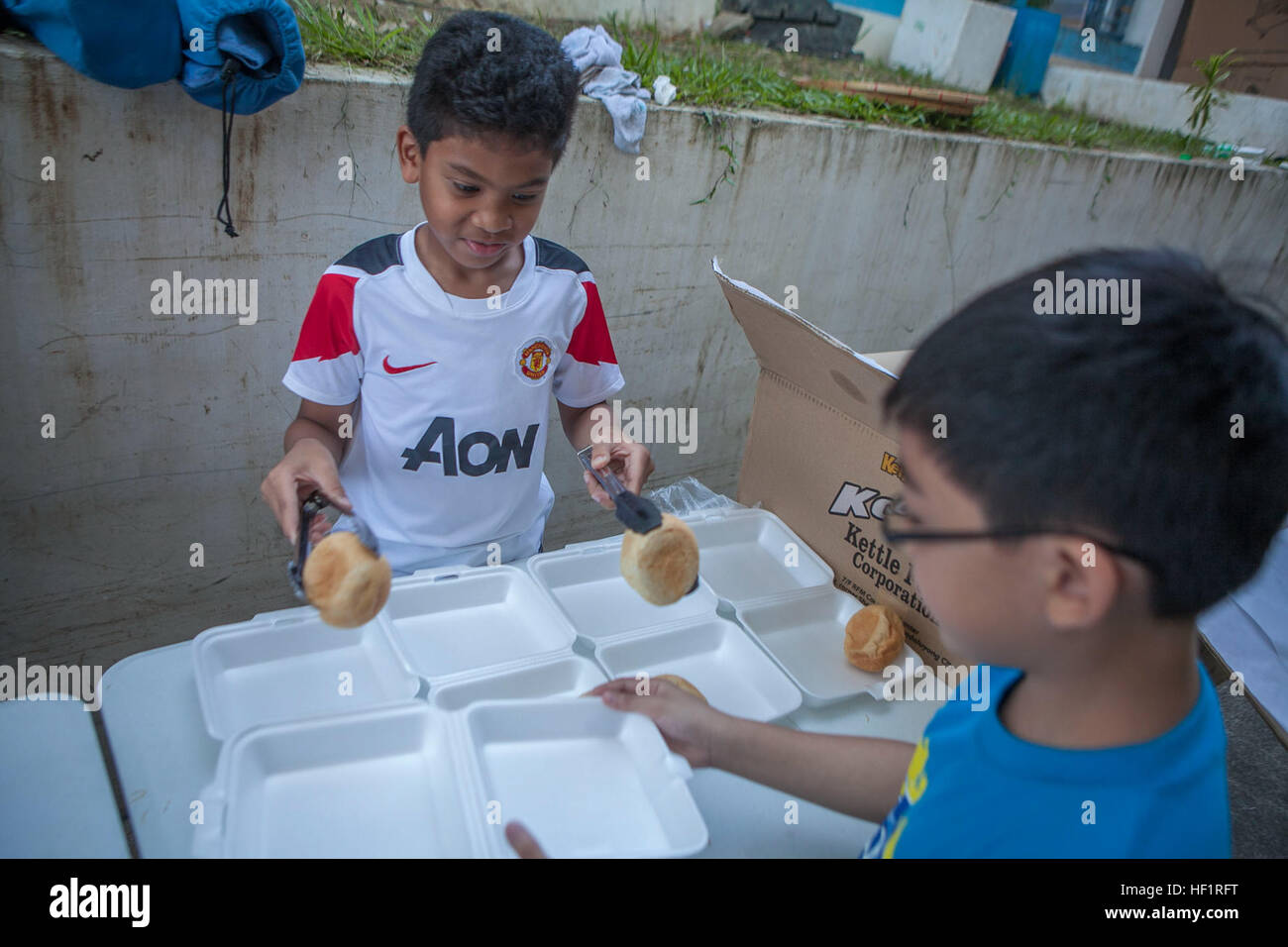 Children volunteer their time to prepare and serve food for evacuees Nov. 17 as they deplane at Villamor Air Base. - Stock Image