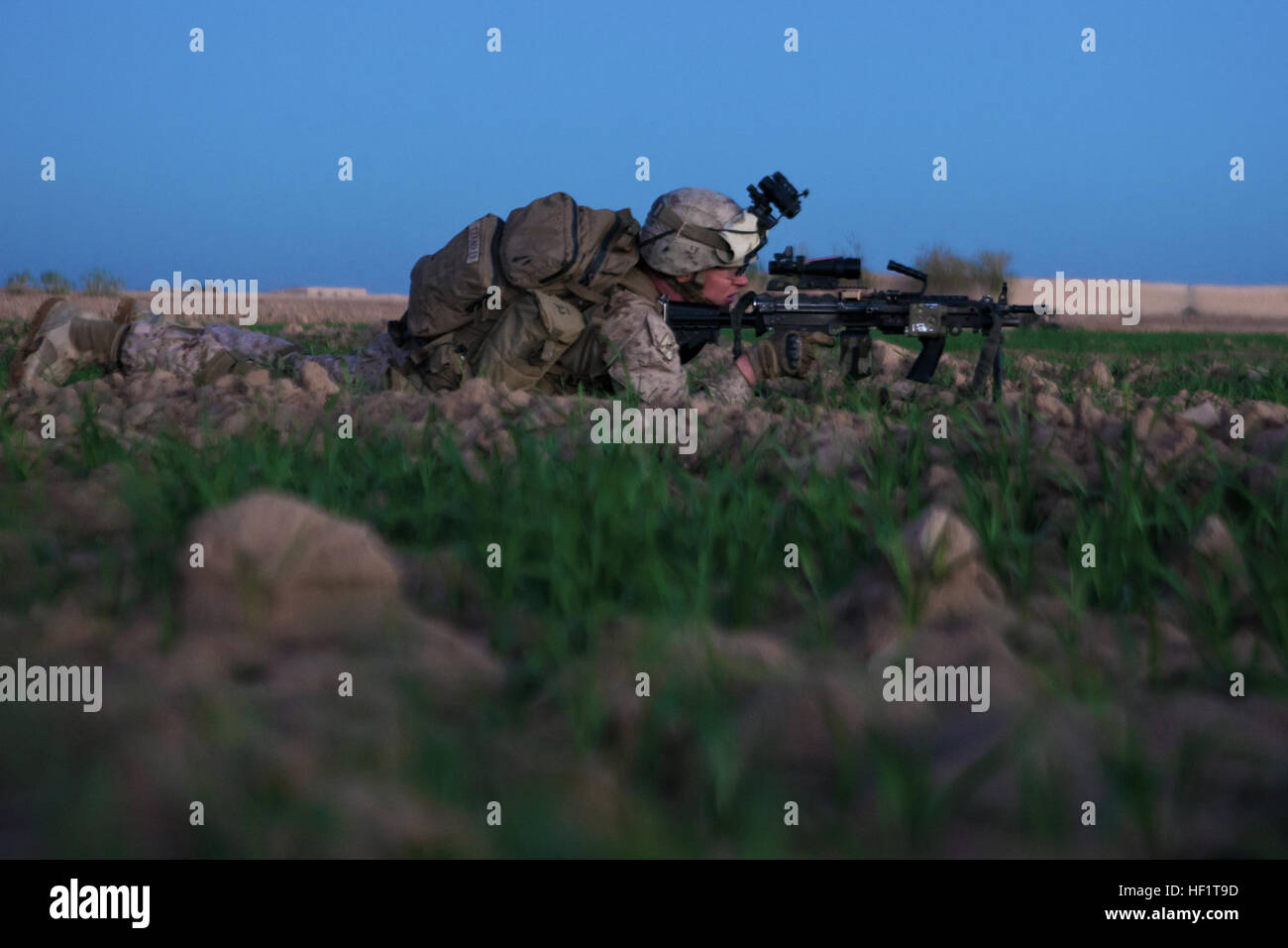 Lance Cpl. Nathan Chandler, a Logan, Ohio, native and machine gunner with 1st Battalion, 9th Marines, hunkers down Stock Photo