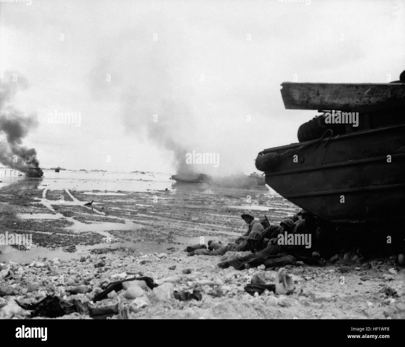 An amphibious tractor burns on the beach as Marines take shelter under a duck.  Peleliu, September 1944.  Pfc. John - Stock Image