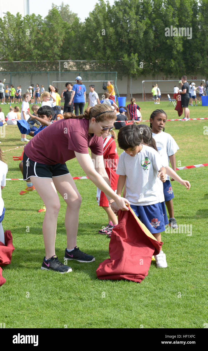 2nd Lt. Katharine Donovan helps a child, from the American School of Doha in Qatar, prepare for a sack race during - Stock Image
