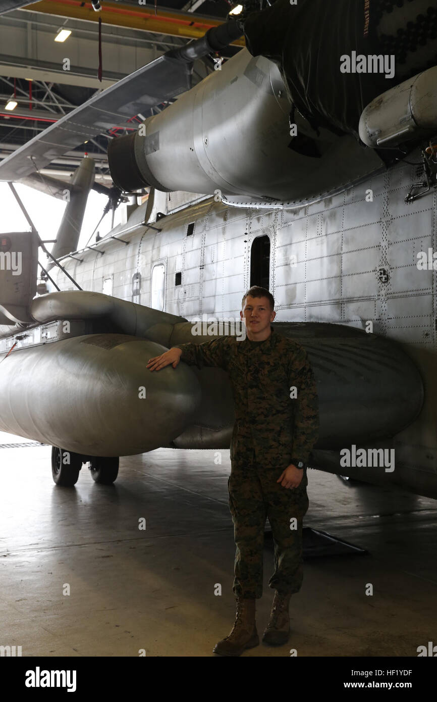 Cpl. Johnathan D. Patterson poses beside a CH-53E Super Stallion inside of the Marine Heavy Helicopter Squadron - Stock Image