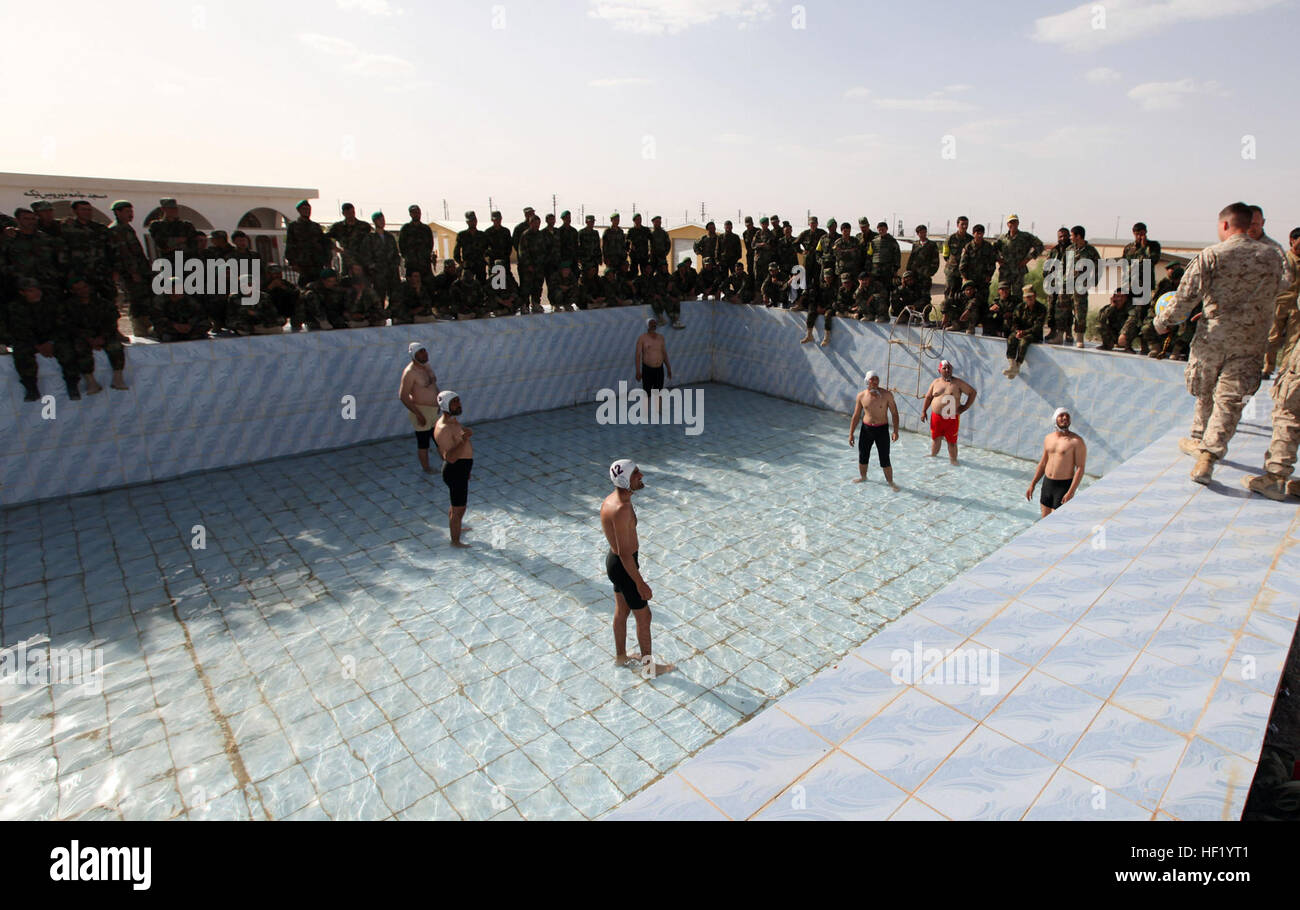 Dozens of spectators gather around the outside of the pool, all wanting to see the newly formed water polo team - Stock Image