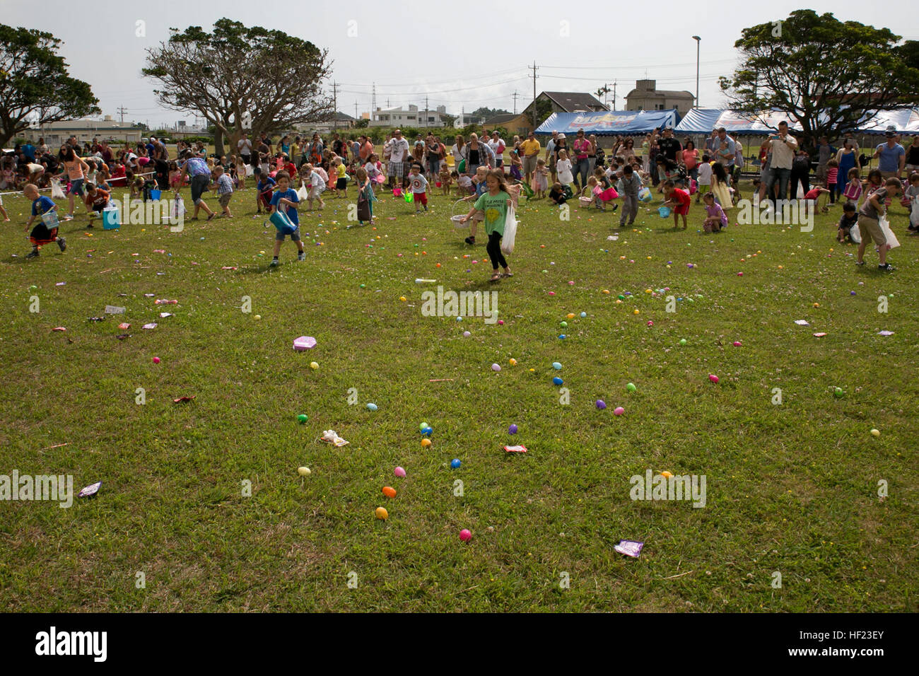 Children dash around a field to collect Easter eggs April 19 at the 'Camp Eggstravaganza' outside the Camp - Stock Image
