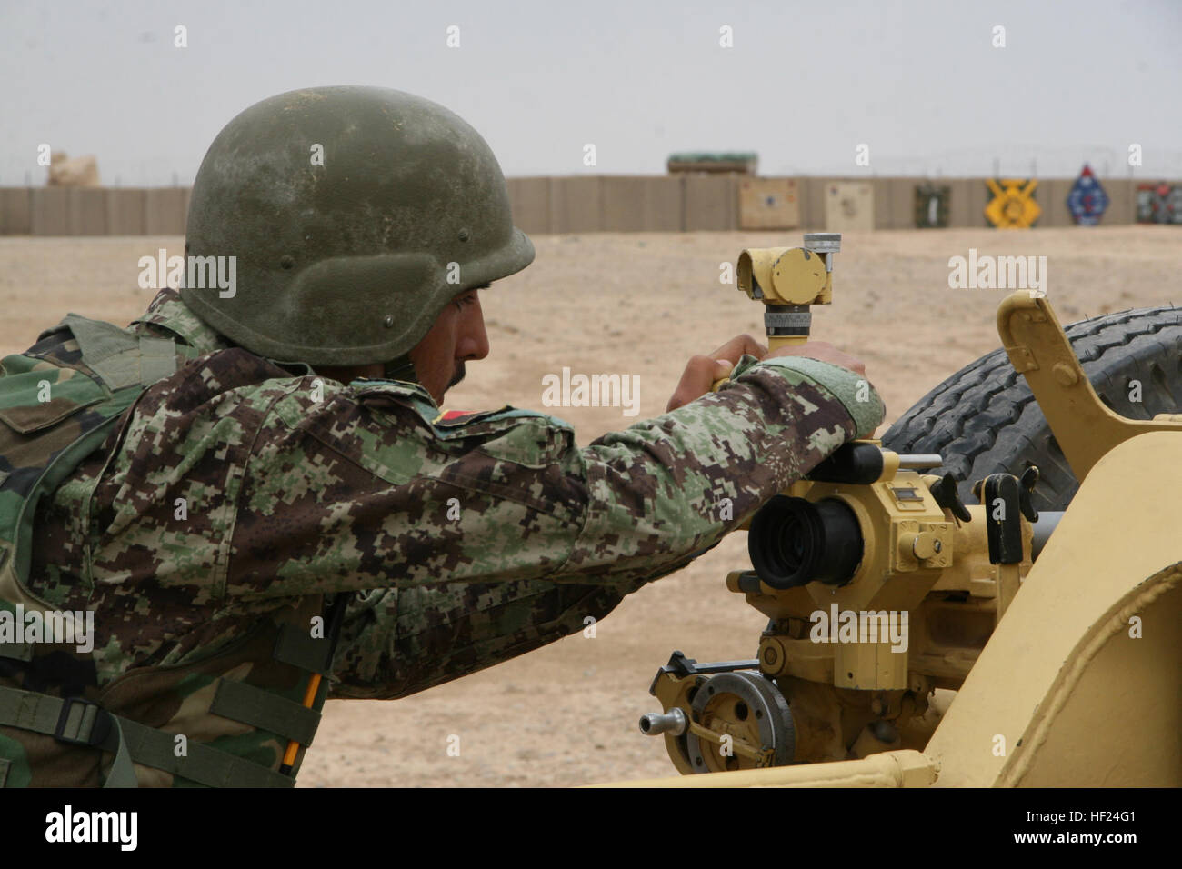 An Afghan National Army soldier with the 215th Corps carefully makes adjustments to the D-30 122 mm howitzer during - Stock Image