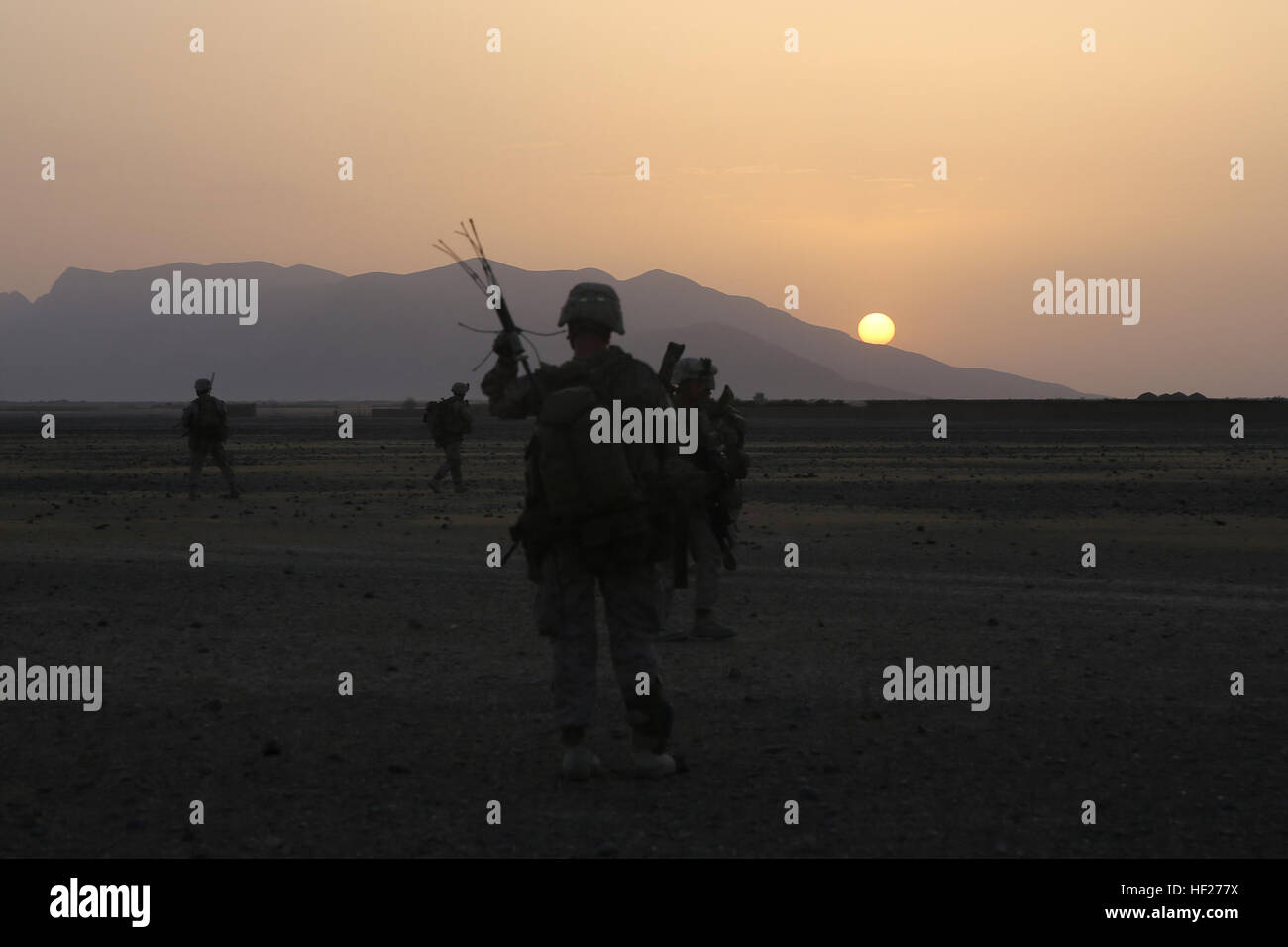 Marines with Bravo Company, 1st Battalion, 7th Marine Regiment, maneuver into a village as the run rises in Helmand - Stock Image