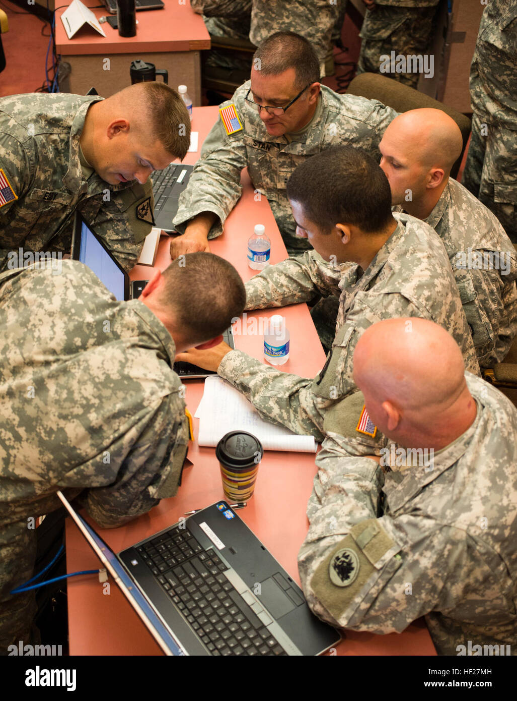 Gathering around a single laptop, Team National Guard maps out a plan to win during the U.S. Army's 'Cyber Center Stock Photo