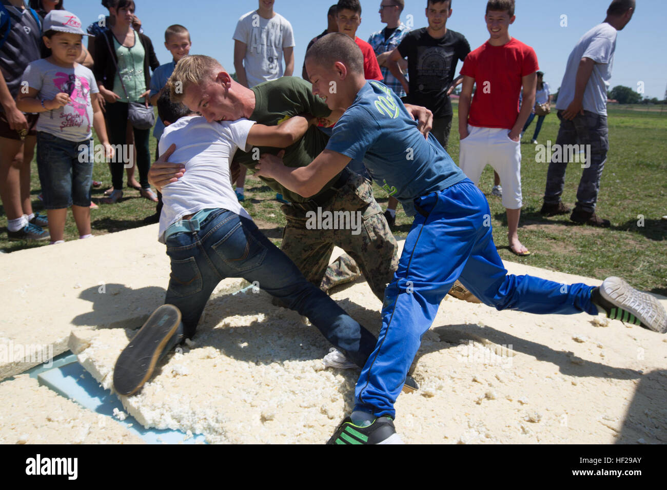 ... from 3rd Battalion, 8th Marine Regiment, plays with two Romanian boys  while demonstrating MCMAP techniques during the last children's event ...