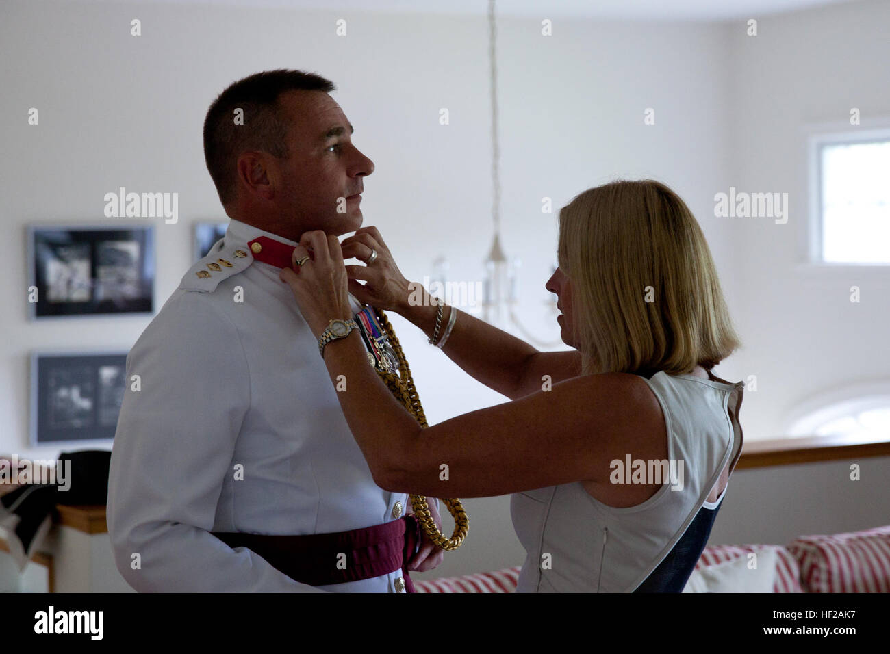 Helen Lister, right, adjusts the uniform collar of her husband, British Royal Marine Attache Col. Al Lister, at Stock Photo